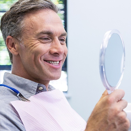 Man looking at smile in mirror