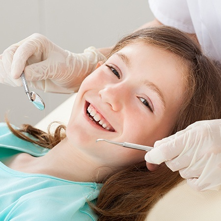 Smiling young girl receiving dental exam