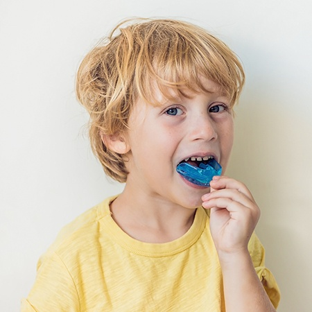 Child placing mouthguard