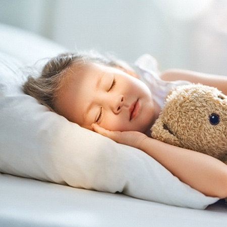 Young girl sleeping peacefully at night with teddy bear