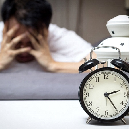 man exhausted alarm clock sounding